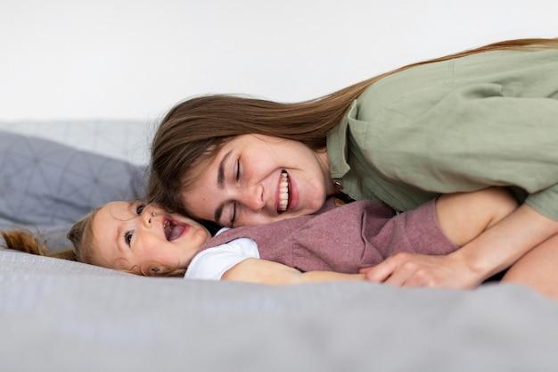 Feliz mãe e menina na cama