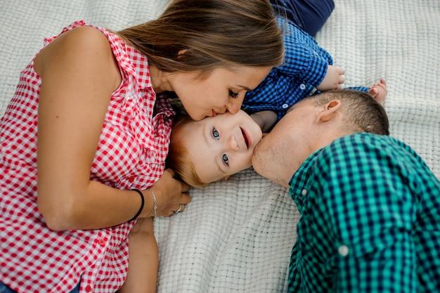 Feliz mãe e pai beijando seu filho vestido com as camisas quadriculadas, deitado sobre a manta no parque