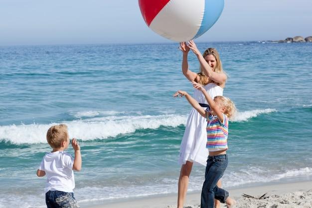 Feliz mãe e seus filhos brincando com uma bola