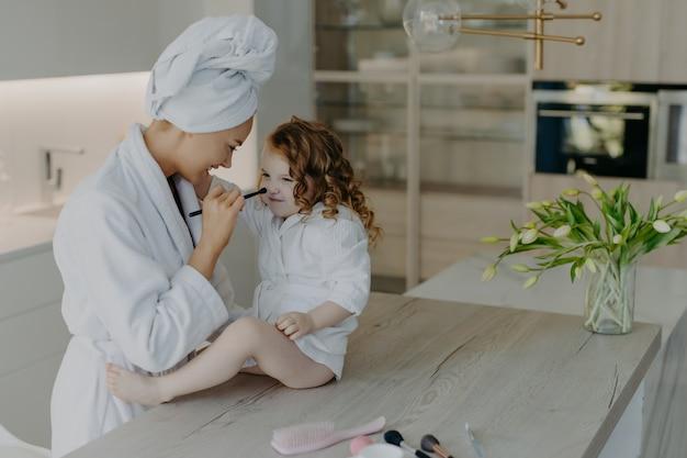 Feliz mãe europeia mantém escova cosmética no nariz da filha e aplica pó facial vestido com roupão de banho branco e macio