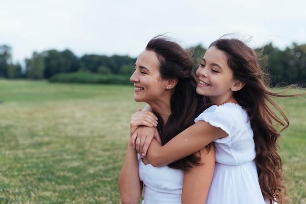 Feliz, mãe filha, abraçando, ao ar livre