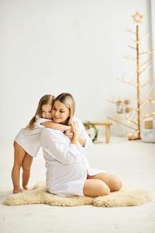 Feliz mãe grávida e suas filhas se abraçam