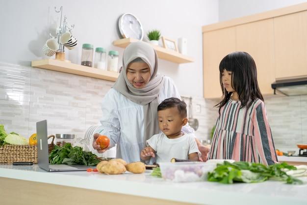 Feliz mãe muçulmana e seus filhos cozinham e se divertem juntos em casa preparando o jantar iftar