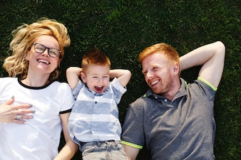 Feliz mãe, pai e seu filho pequeno encontram-se na grama verde