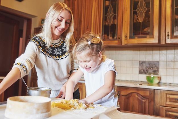 Feliz mãe sorridente na cozinha assa biscoitos com a filha.