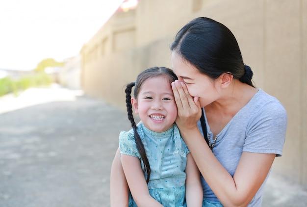 Feliz mãe sussurrando algo secreto para sua orelha de filha pequena.
