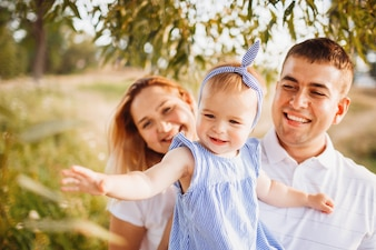 Feliz, mamãe e papai segurar, filha pequena, ligado, seu, braços, ficar, em, a, raios, de, noite, sol
