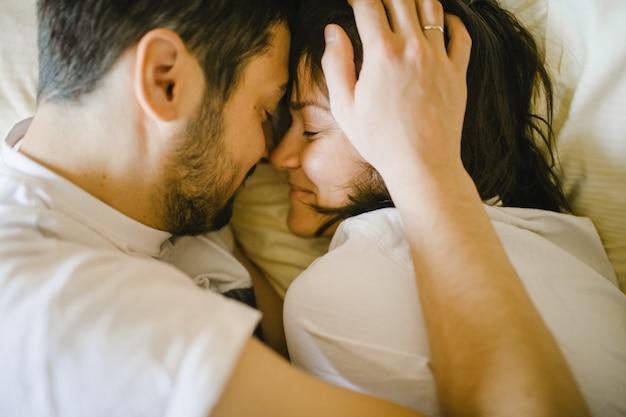 Feliz marido e mulher abraçando na cama