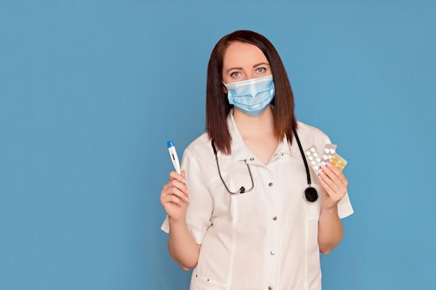 Feliz médico com um jaleco branco com um estetoscópio tem remédio e um termômetro nas mãos