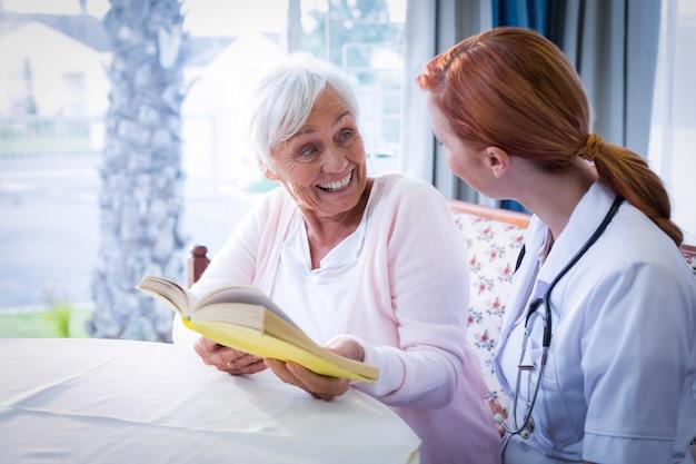 Feliz médico e paciente lendo um livro