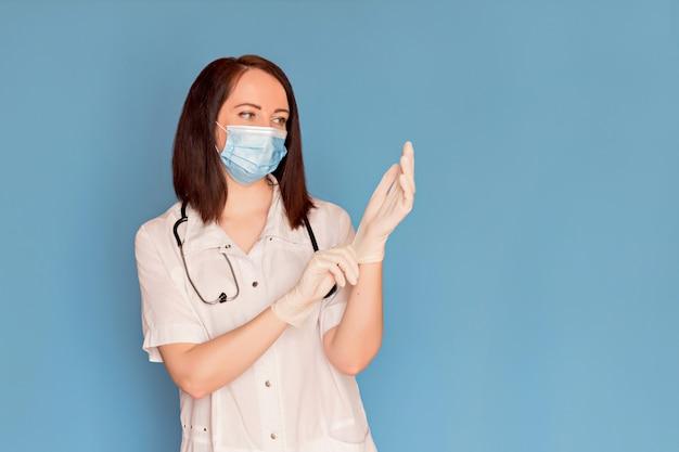 Feliz médico feminino em máscara médica coloca luvas médicas com um estetoscópio. copie o espaço