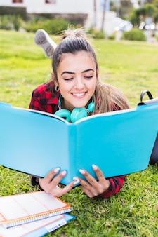 Feliz, menina adolescente, mentindo, gramado, lendo livro