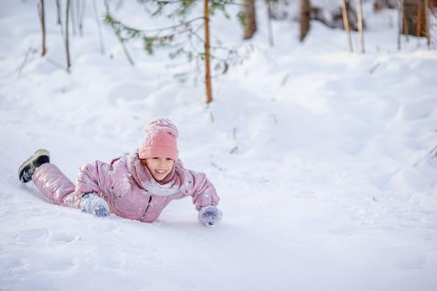 Feliz menina adorável trenó em dia de inverno nevado.