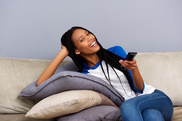 Feliz, menina americana africana, segurando, controle remoto, sentar sofá, e, observar tv