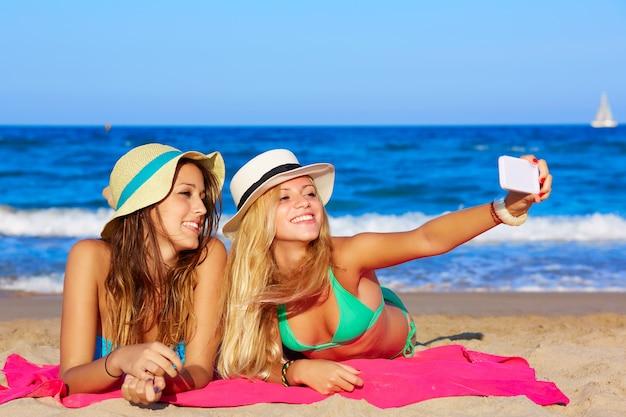 Feliz menina amigos selfie retrato deitado na praia