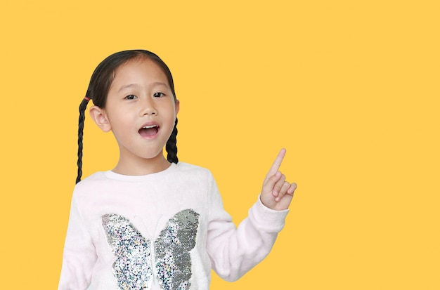 Feliz menina asiática apontando o dedo indicador para cima