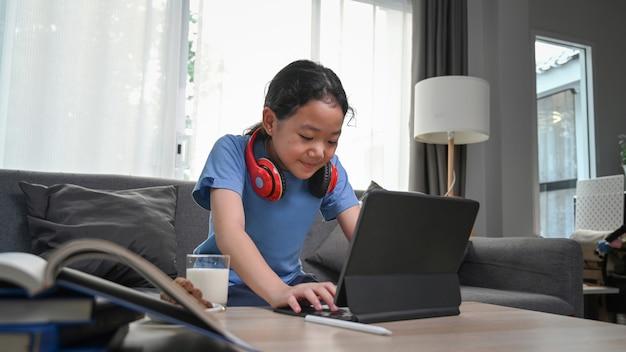 Feliz menina asiática assistindo desenhos animados online no tablet digital enquanto está sentado no sofá.