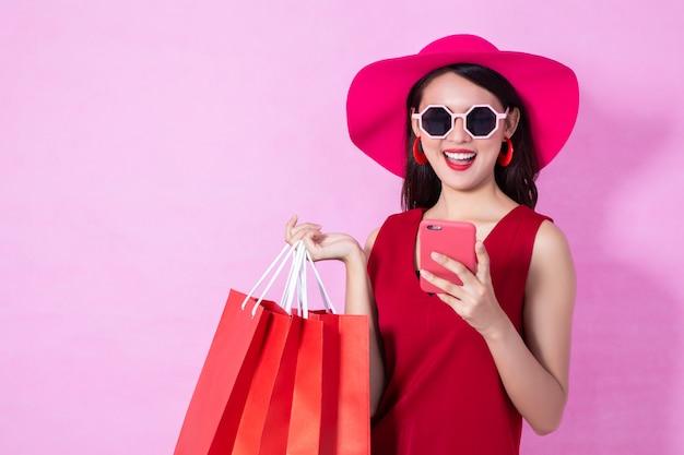 Feliz menina asiática bonita vestido vermelho segurando sacolas de compras e telefone inteligente a desviar o olhar no fundo rosa