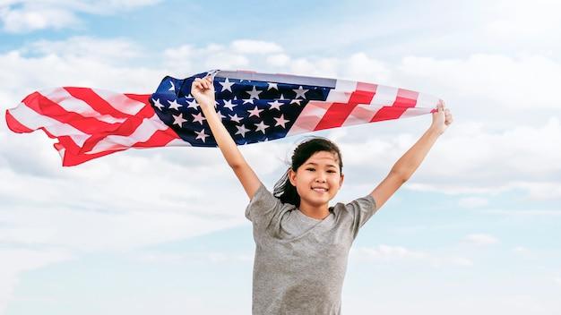 Feliz menina asiática com bandeira americana eua comemorar 4 de julho