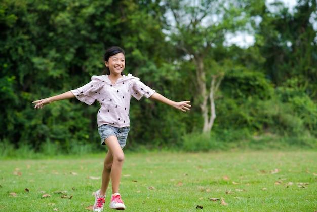 Feliz, menina asiática, com, executando, ligado, grama verde, parque