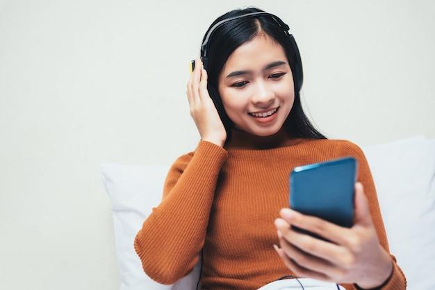 Feliz menina asiática com fones de ouvido, ouvindo música.