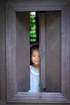 Feliz menina asiática em pé e abra a janela