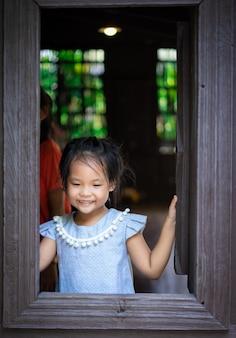 Feliz menina asiática em pé junto à janela