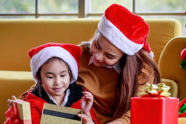 Feliz menina asiática família filha usa camisola vermelha e branca chapéu de papai noel sentado com a mãe surpreendente emocionante quando abrir a caixa de presente presente comemorar a véspera de natal perto do pinheiro de natal na sala de estar.