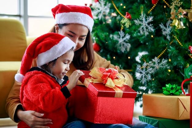 Feliz menina asiática família filha usa camisola vermelha e branca chapéu de papai noel sentado com a mãe unboxing caixa de presente aberto comemorando a véspera de natal perto de pinheiro de natal na sala de estar em casa.