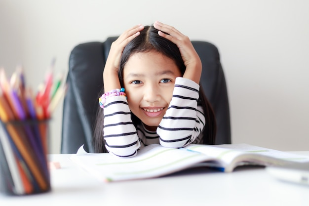 Feliz menina asiática fazendo lição de casa e sorrindo