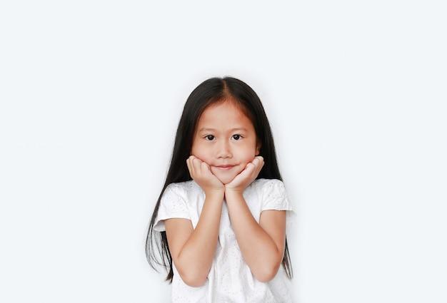 Feliz menina asiática mantém as duas mãos nas bochechas