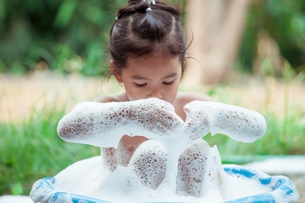 Feliz menina asiática se divertindo e brincando com espuma