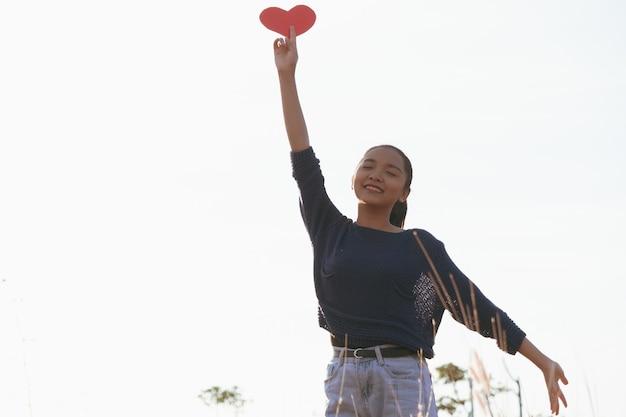 Feliz menina asiática segurar papel coração vermelho com tempo de rim ligth no prado.