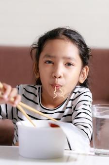 Feliz menina asiática sentado à mesa branca para comer macarrão instantâneo