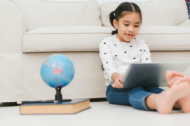 Feliz menina asiática usando computador portátil