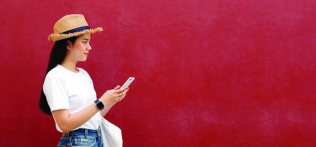 Feliz menina asiática usando telefone celular em cima de fundo parede vermelha