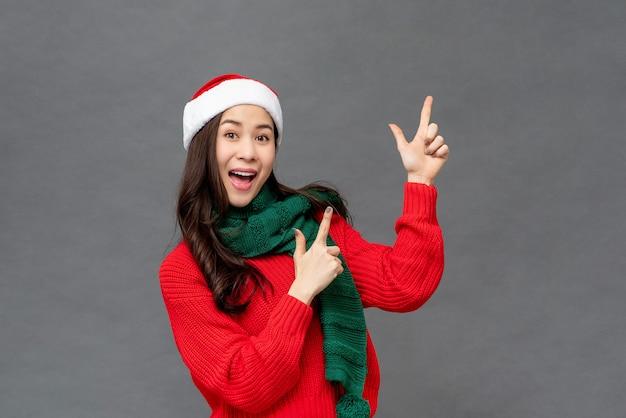 Feliz menina asiática vestindo trajes de natal, apontando as mãos para o espaço vazio de lado