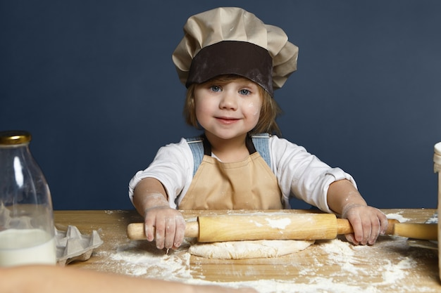 Feliz menina bonitinha achatando massa usando rolo enquanto ajuda a mãe a cozinhar torta para o jantar. doce criança do sexo feminino com olhos azuis fazendo biscoitos na cozinha, olhando e sorrindo para a câmera