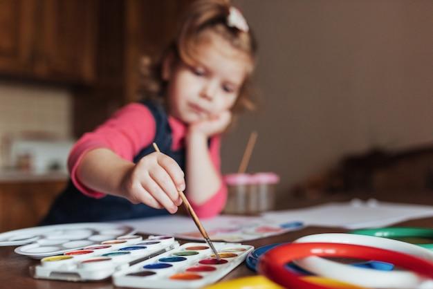Feliz menina bonitinha, adorável criança em idade pré-escolar, pintando com wate