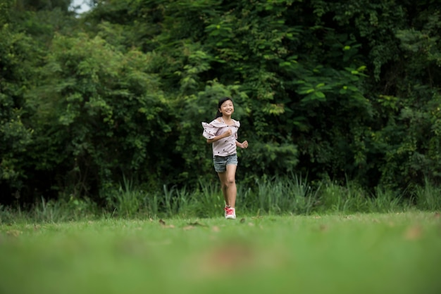 Feliz menina bonitinha correndo na grama no parque
