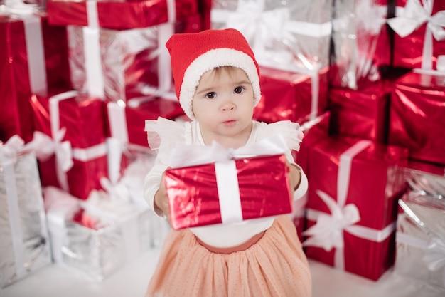 Feliz menina bonitinha em lindo vestido segurando a caixa vermelha e posando com muitos presentes. conceito de férias de natal