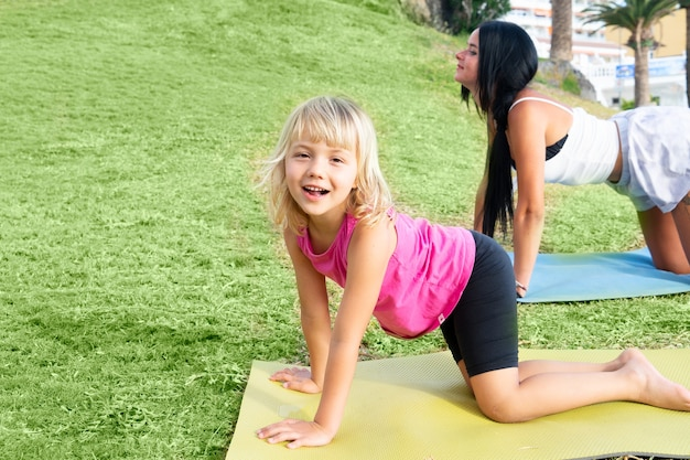 Feliz menina bonitinha em roupas esportivas, olhando para a câmera e sorrindo em pé no tapete de ioga e se exercitando na beira-mar durante as férias com a família. crianças e conceito de estilo de vida ativo e saudável