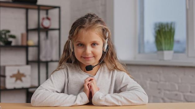 Feliz menina bonitinha usa fone de ouvido sorrindo para a câmera da web. gravação de vlog, videoconferência online, videochamada.