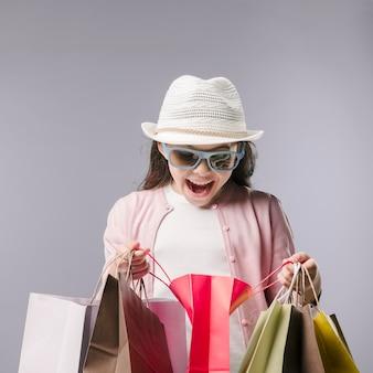 Feliz, menina, com, bolsas para compras, em, estúdio