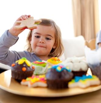 Feliz menina comendo confeitaria em casa