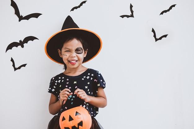 Feliz menina criança asiática em trajes e maquiagem se divertindo na celebração do dia das bruxas
