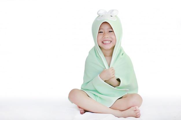 Feliz menina criança asiática sorrindo corpo de capa debaixo da toalha depois do banho sentado na cama