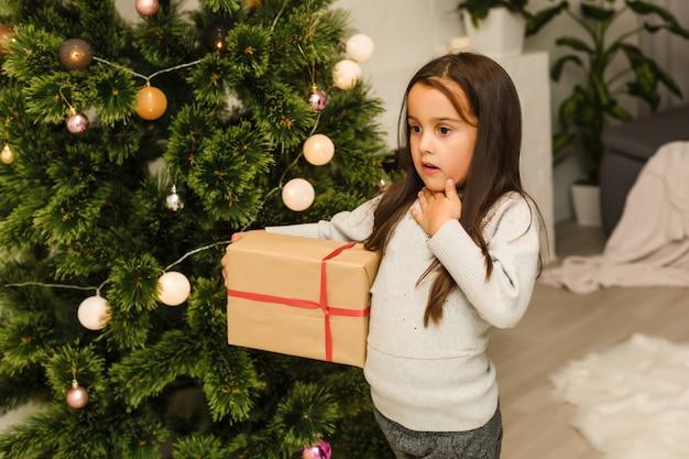 Feliz, menina, desgastar, natal, pijama, tocando, por, um, lareira, em, sala de estar, ligado, natal