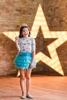 Feliz, menina, ficar, frente, iluminado, estrela, contra, parede tijolo, apontar dedo, cima