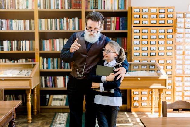 Feliz menina loira adolescente de óculos, segurando um livro nas mãos enquanto ouve seu velho avô inteligente, professor ou bibliotecário